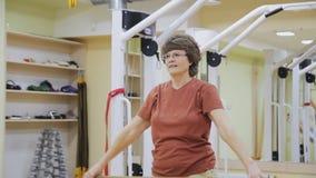 La femme agée s'étirant, faisant la physiothérapie s'exerce avec le bâton dans la chambre de forme physique Gymnastique saine act banque de vidéos