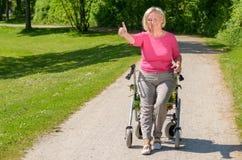 La femme agée s'assied dans le marcheur à roues sur le chemin de parc Photo libre de droits