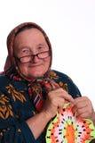 La femme agée, tricotant la serviette Image stock