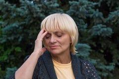La femme agée a un mal de tête et touche sa tête Photos stock