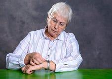 La femme agée velue grise a réglé sa montre image stock