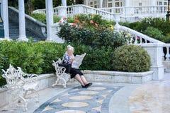 La femme agée seule lit le journal Images libres de droits