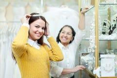 La femme aide la jeune mariée en choisissant le diadème nuptiale Images stock