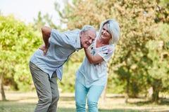 La femme aide le vieil homme avec douleurs de dos Images stock