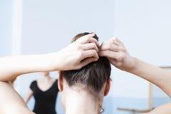 La femme ajuste des cheveux pendant la classe de ballet Images stock