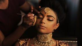 La femme ajuste le maquillage sur le visage renversant de la jeune mariée indienne tandis qu'elle repose le calme sur la chaise banque de vidéos