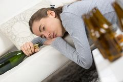 La femme alcoolique d'intoxiqué se trouvant sur le sofa hangovered avec des bouteilles images stock