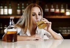 La femme alcoolique ivre a gaspillé le boire sur le whisky écossais dans la barre images stock