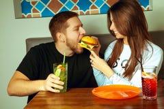 La femme alimente l'ami avec l'hamburger Photo libre de droits