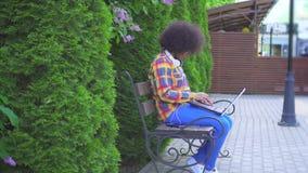 La femme américaine noire avec une coiffure Afro utilise un ordinateur portable se reposant sur le banc sur la rue banque de vidéos