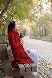 La femme anonyme appréciant la tasse de café à emporter le jour froid ensoleillé d'automne s'asseyent sur le banc photographie stock