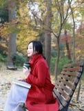 La femme anonyme appréciant la tasse de café à emporter le jour froid ensoleillé d'automne s'asseyent sur le banc photos libres de droits