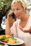 La femme appelle pendant une coupure dans le restaurant Image stock