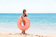 La femme appelle pour nager en mer et ondule sa main Fille d?tendant avec le beignet sur la plage et jouant avec l'anneau gonflab photos stock