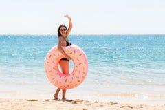 La femme appelle pour nager en mer et ondule sa main Fille d?tendant avec le beignet sur la plage et jouant avec l'anneau gonflab image libre de droits