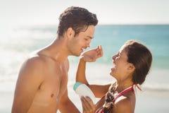 La femme appliquant la lotion de protection solaire équipe dessus le visage Photo stock