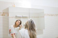 La femme appliquant le matin composent dans le miroir de la salle de bains photo libre de droits