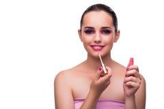 La femme appliquant le rouge à lèvres d'isolement sur le blanc Photo libre de droits