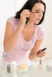 La femme appliquent le mascara dans le miroir avant de salle de bains Image stock