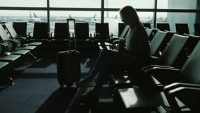 La femme apprécie l'ordinateur portable et boit du café sur le terminal d'aéroport Photographie stock