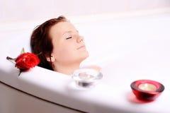 La femme apprécie la bain-mousse dans la baignoire. Photographie stock
