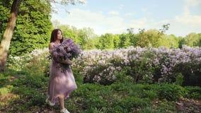 La femme apprécie le parfum du lilas banque de vidéos