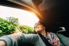 La femme apprécient avec la vue de la fenêtre de voiture dans le déplacement en automobile Photo libre de droits
