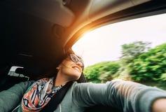La femme apprécient avec la vue de la fenêtre de voiture dans le déplacement en automobile photos stock