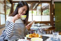 La femme apprécient le petit déjeuner dans le café Image stock