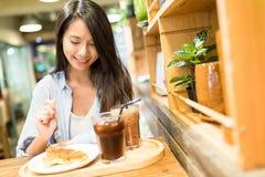 La femme apprécient sa nourriture dans le restaurant image stock