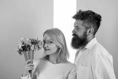 La femme appr?cient des fleurs de bouquet de parfum Les couples dans l'amour heureux c?l?brent l'anniversaire L'homme avec la bar photo libre de droits