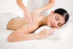 La femme appréciant un sel frottent le massage Photos stock