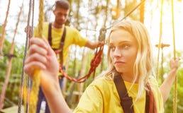 La femme apprend s'élever dans le jardin de corde raide ou la forêt s'élevante photo stock
