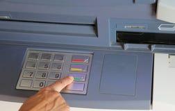 La femme appuie sur les boutons d'un distributeur automatique de billets pour prendre l'argent Images libres de droits