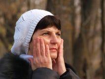 La femme appuyant des mains aux joues Photographie stock libre de droits