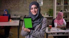 La femme arabe de sourire impressionnante dans le hijab gris est écran de vert de démonstration sur son comprimé tout en se tenan banque de vidéos