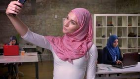 La femme arabe de sourire impressionnante prend des selfies et juge son téléphone concentré sur lui, se tenant devant l'autre séa clips vidéos