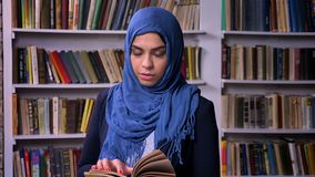 La femme Arabe impressionnante dans le hijab bleu-foncé tient le livre dans la bibliothèque, se tenant calmement et le regard sûr clips vidéos