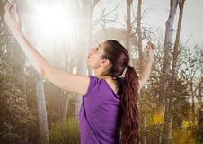 La femme arme en air contre les arbres troubles avec la fusée Photos stock