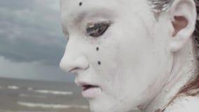 La femme artistique de représentation couverte en peinture blanche ouvre la bouche sur le bord de mer clips vidéos