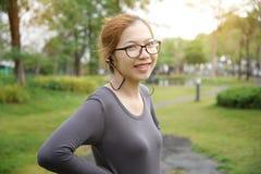 La femme asiatique écoute la musique Photographie stock