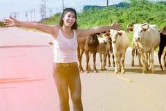 La femme asiatique assez jeune apprécient le jour d'été avec la vache sur une route Photo libre de droits