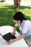 La femme asiatique attirante est à l'extérieur avec l'ordinateur portatif Images libres de droits
