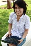 La femme asiatique attirante est à l'extérieur avec l'ordinateur portatif Image stock