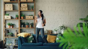 La femme asiatique attirante a l'amusement à la maison écoutant la musique par des écouteurs tenant le smartphone, chantant et banque de vidéos