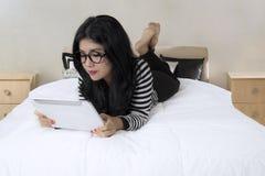 La femme asiatique attirante utilise le comprimé sur le lit photo stock