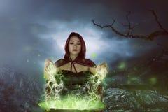 La femme asiatique avec du charme de sorcières préparant un breuvage magique Photos libres de droits