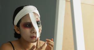 La femme asiatique crée le maquillage de Halloween sur le visage banque de vidéos