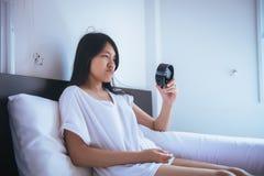 La femme asiatique déteste obtenir se réveiller soumis à une contrainte tôt, femelle étirant sa main à l'alarme de sonnerie pour  photos stock