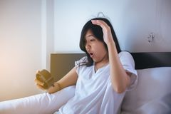 La femme asiatique déteste obtenir se réveiller soumis à une contrainte tôt, femelle étirant sa main à l'alarme de sonnerie pour  image libre de droits